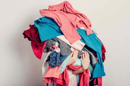 10 great reasons to hire a stylist, Pile of clothing, messy clothing, woman holding clothing, woman holding pile of clothing, unfolded laundry, pile of laundry